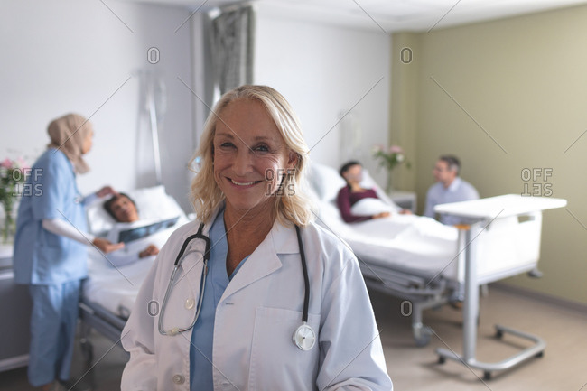 Portrait of Caucasian female doctor smiling in the ward at hospital. In the background diverse doctors are interacting with their patients next to the beds.