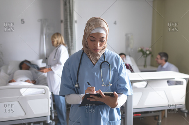 Front view of mixed race female doctor in hijab writing on clipboard in the ward at hospital. In the background diverse doctors are interacting with their patients.