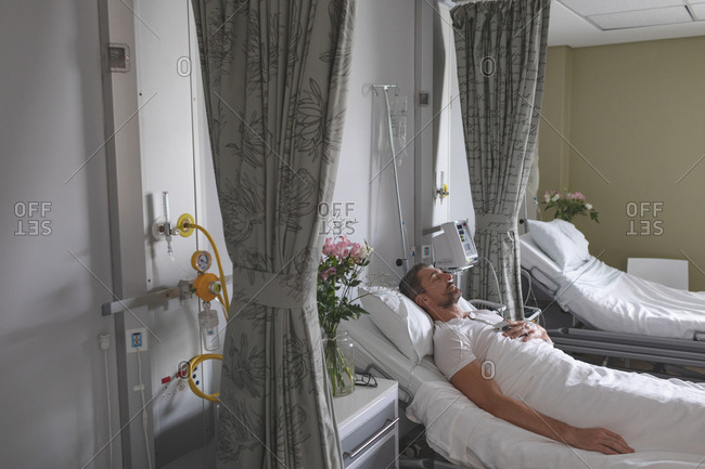 Side view of Caucasian male patient sleeping with his hand on chest in bed in the ward at hospital