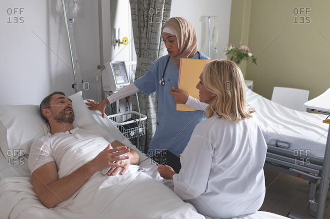 Side view of diverse female doctors interacting with Caucasian male patient in the ward at hospital