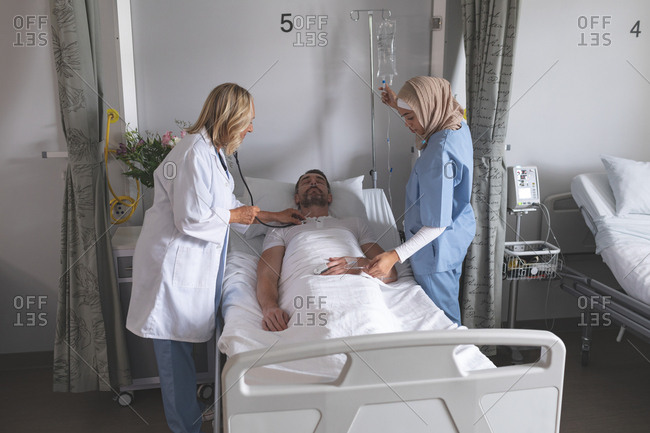 Side view of Caucasian female doctor examining Caucasian male patient with stethoscope in the ward at hospital. On the right side of the bed mixed-race female nurse in hijab is assisting Caucasian female doctor.