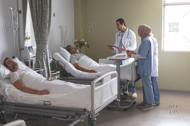 Side view of diverse doctors interacting with senior mixed-race male patient while Caucasian male patient sleeping in bed next to them in the ward at hospital