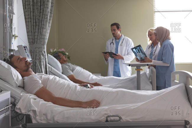 Side view of diverse doctors interacting with mixed-race male patient  while Caucasian male patient sleeping in bed next to them  in the ward at hospital.