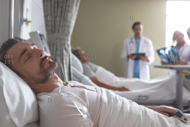 Side view of Caucasian male patient sleeping on bed in the ward at hospital. In the background diverse doctors discussing x-ray with mixed-race male patient.