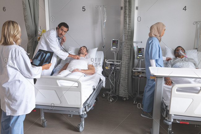 Side view of Caucasian male doctor examining male patient with stethoscope while female doctor looks at x-ray in the ward at hospital.