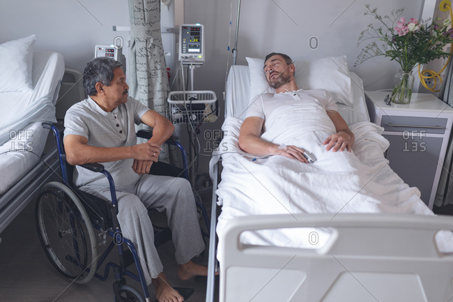 Front view of diverse male patients interacting with each other in the ward at hospital. Caucasian male patient lying in bed while mixed-race patient sits in wheelchair.