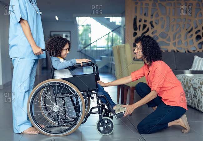 Side view of mixed-race mother consoling her disabled son in the lobby at hospital.