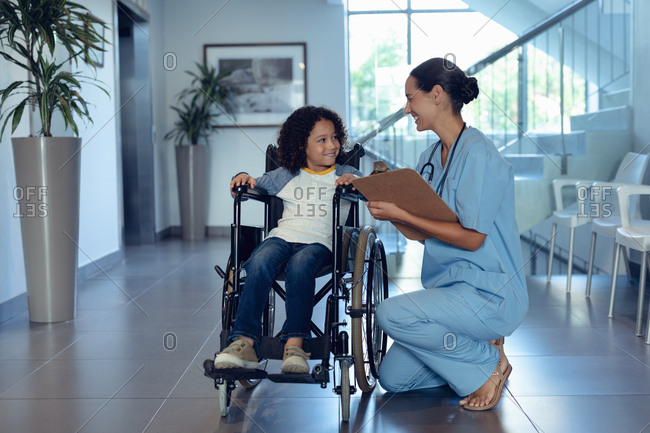 Side view of happy Caucasian female doctor interacting with disabled mixed-race boy in the corridor at hospital. Boy is sitting in wheelchair.