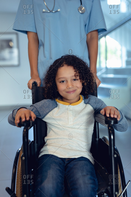Portrait of disabled mixed-race boy in wheelchair with female doctor in the corridor at hospital