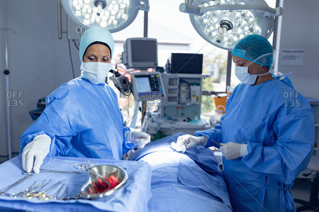 Side view of diverse female surgeons performing surgery in operation room at hospital