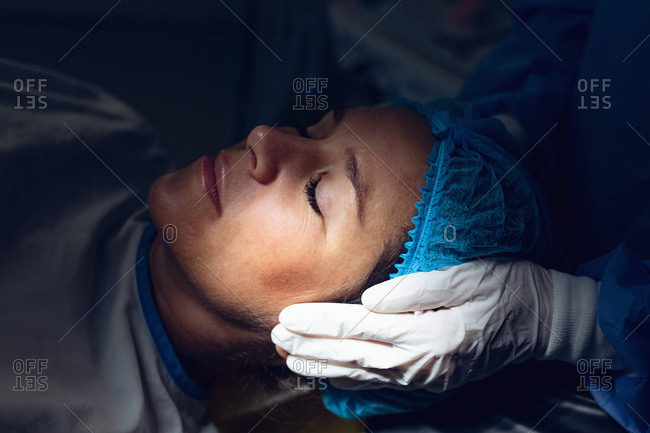 Closed-up of surgeon comforting pregnant Caucasian woman during labor in operation theater at hospital