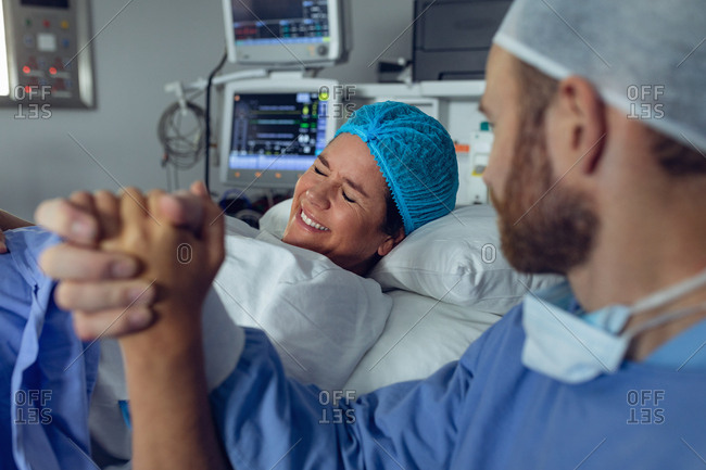 Side view of Caucasian man comforting pregnant woman during labor in operation theater at hospital