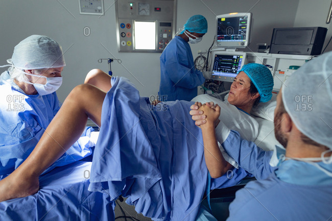 Side view of diverse surgeons examining pregnant Caucasian woman during delivery while Caucasian man holding her hand in operating room at hospital