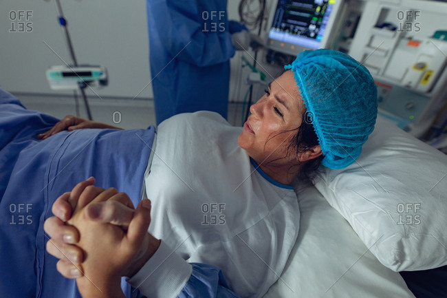 Rear view of Caucasian man comforting pregnant Caucasian woman during labor in operation theater at hospital