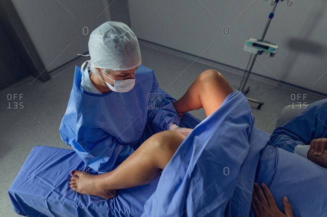 High angle view of Caucasian female surgeon examining pregnant woman during delivery in operating room at hospital