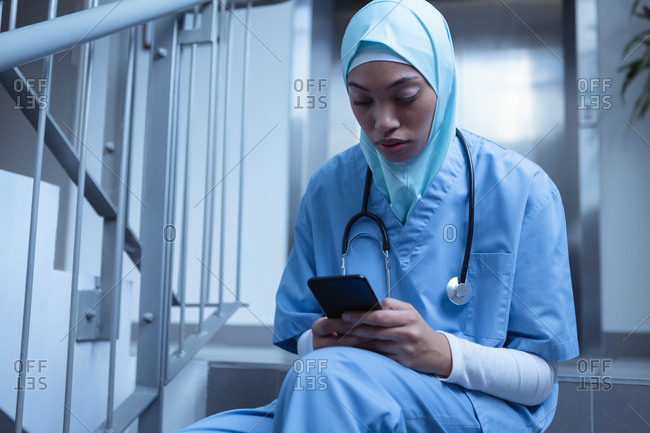 Front view of mixed-race female nurse in hijab using mobile phone on stairs at hospital
