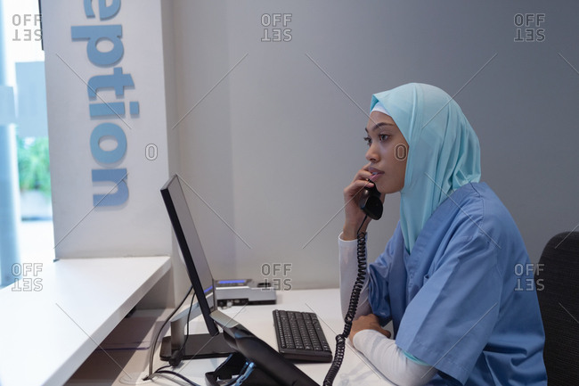 Side view of mixed-race female surgeon in hijab talking on landline at reception in hospital