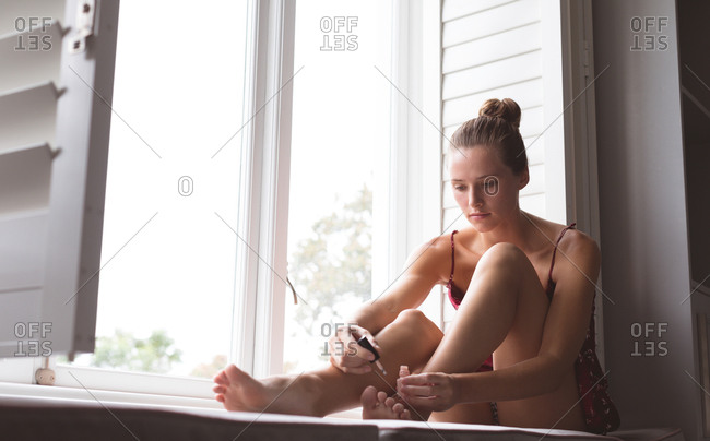 Front view of Caucasian woman applying nail polish to her toenails while sitting on window seat in bedroom at home
