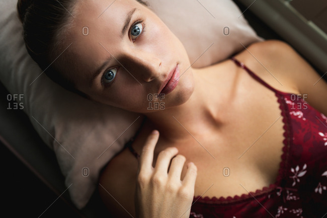 Portrait of Caucasian woman lying on window seat at home