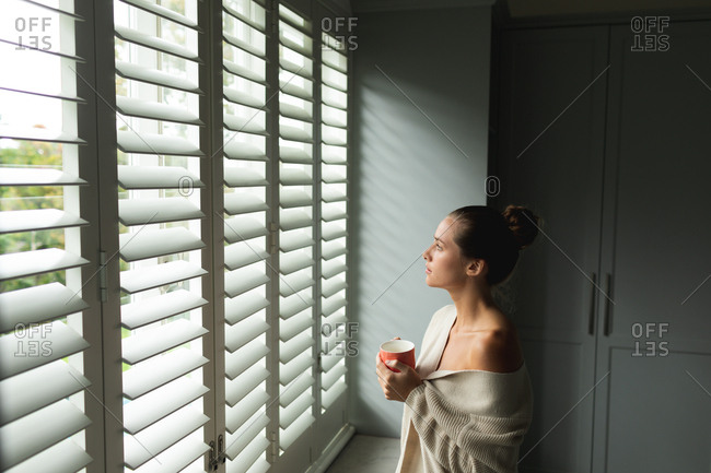 Side view of Caucasian woman with coffee mug looking through window at home