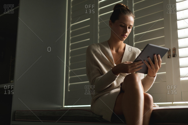 Low angle view of Caucasian woman using digital tablet while sitting on window seat at home