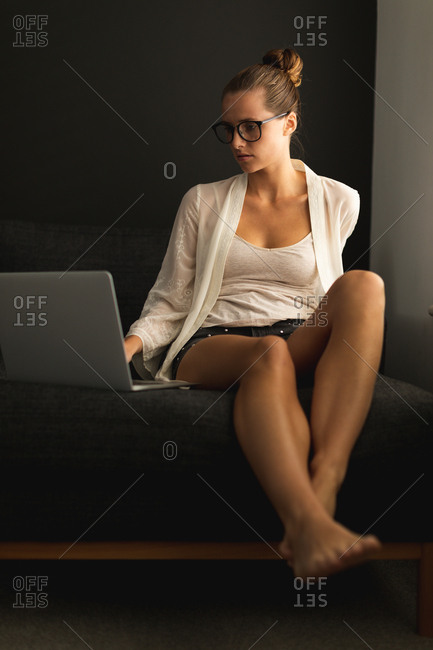 Front view of Caucasian woman using laptop on a sofa in living room at home