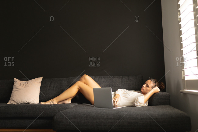 Side view of Caucasian woman using laptop while relaxing on a sofa in living room at home