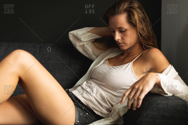 Side view of beautiful Caucasian woman relaxing on a sofa in living room at home