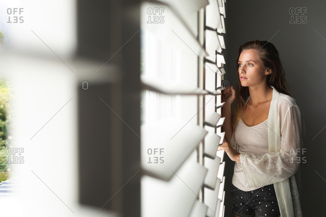 Front view of thoughtful Caucasian woman looking through window blind at home
