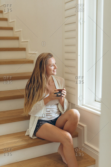 Side view of happy Caucasian woman with coffee cup looking through window while sitting on stairs at home