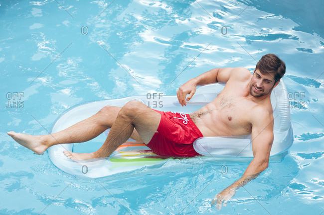 High view of happy Caucasian man relaxing on a inflatable tune in swimming pool