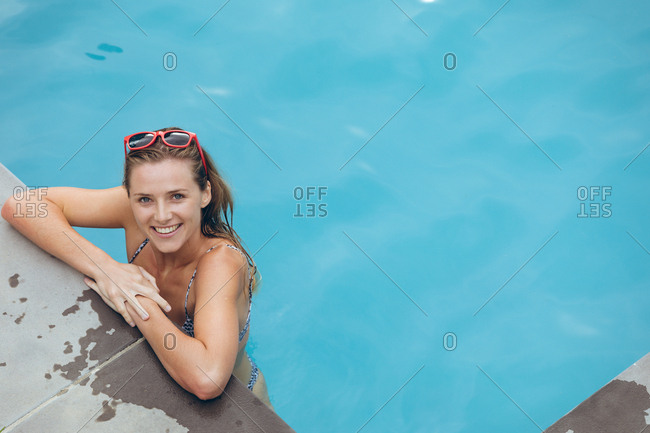 Portrait of happy Caucasian woman standing at the edge of swimming pool