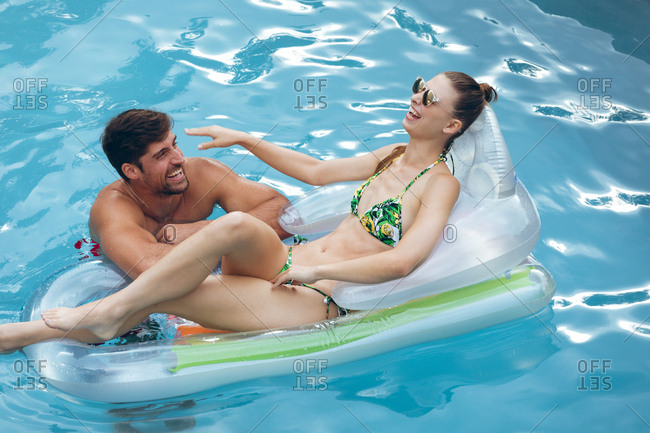 High view of happy Caucasian couple having fun together in swimming pool