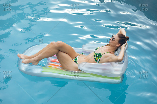 High view of beautiful Caucasian woman in bikini relaxing on a inflatable tube in swimming pool