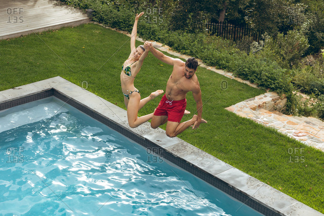 High view of Caucasian couple jumping together in the swimming pool at backyard