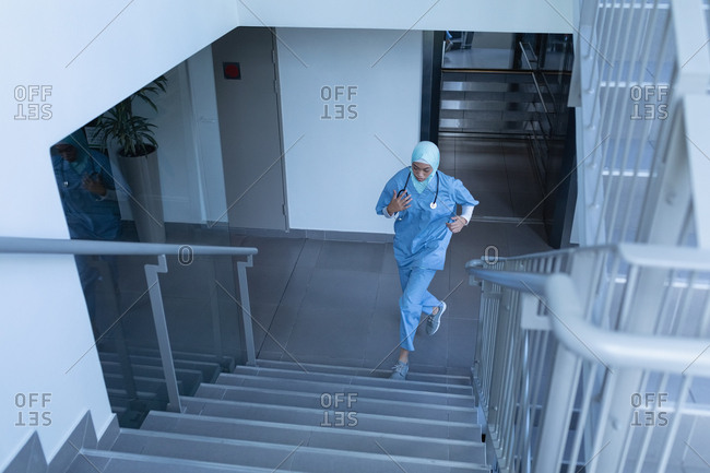 Front view of young mixed race female doctor in hijab running upstairs in the hospital