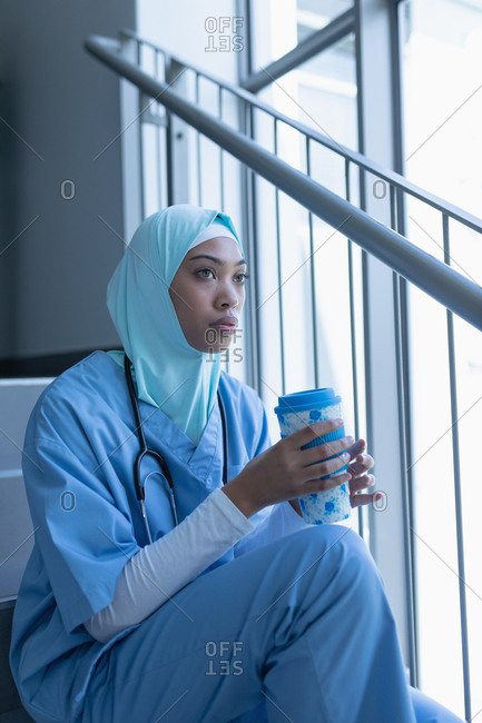 Side view of thoughtful mixed race female doctor in hijab having coffee on staircase in hospital