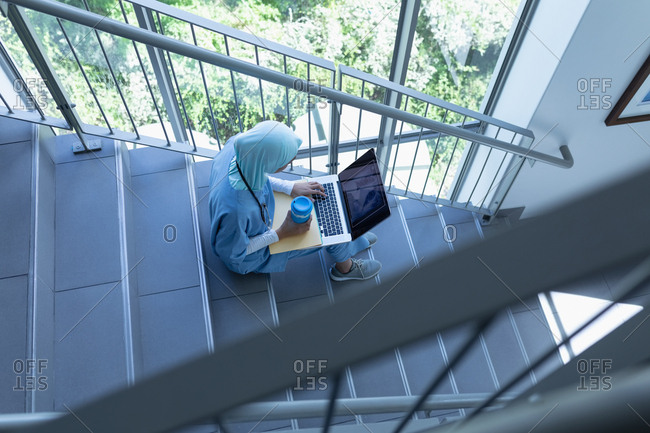 High view of mixed race female doctor in hijab using laptop on staircase in hospital