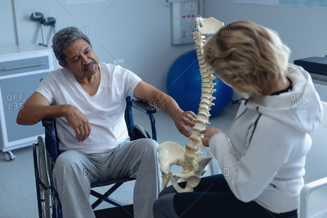 Rear view of Caucasian female physiotherapist explaining spine model to mixed-race male in wheelchair patient in hospital