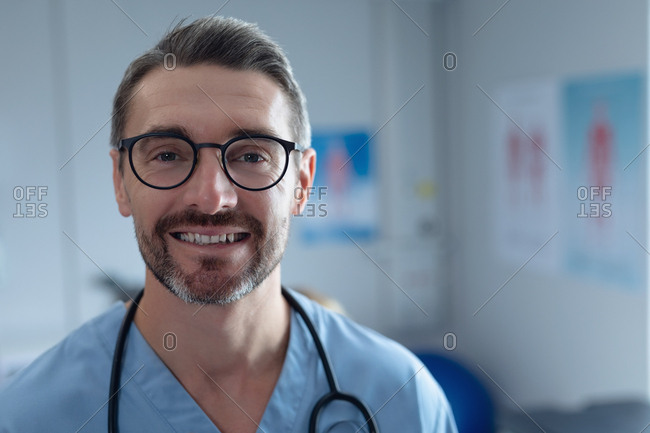 Portrait of mature Caucasian male surgeon with stethoscope around the neck looking at camera in hospital