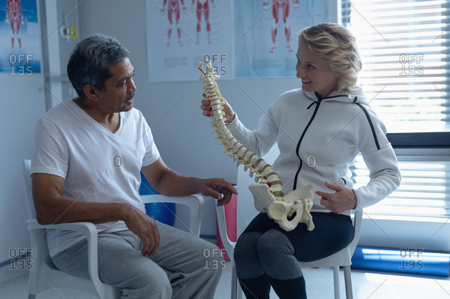 Front view of Caucasian female physiotherapist explaining spine model to male patient in hospital