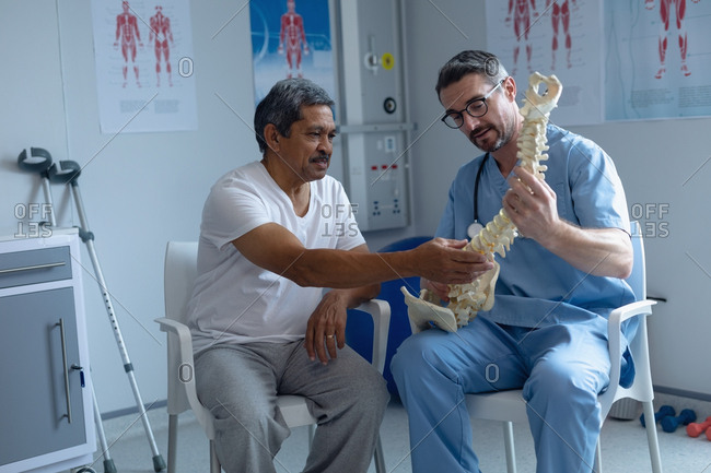Front view of handsome Caucasian male orthopedic surgeon explaining spine model to mixed-race male patient in hospital