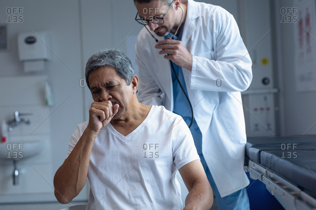 Front view of Caucasian male doctor examining senior mixed-race patient with stethoscope in hospital