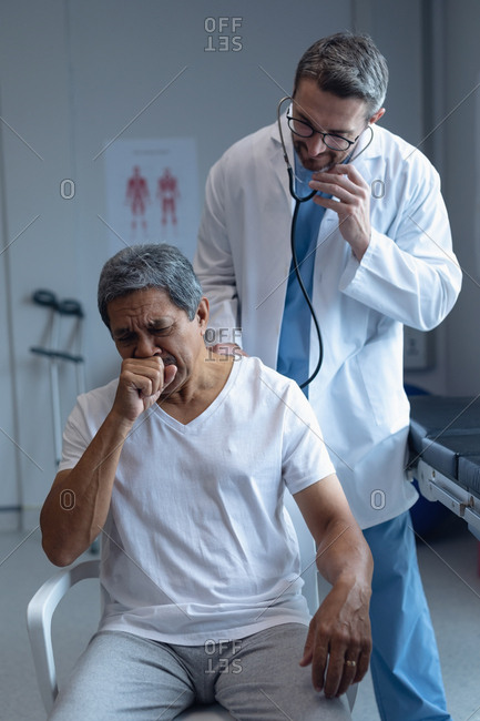 Front view of Caucasian male doctor examining senior mixed-race male patient with stethoscope in hospital