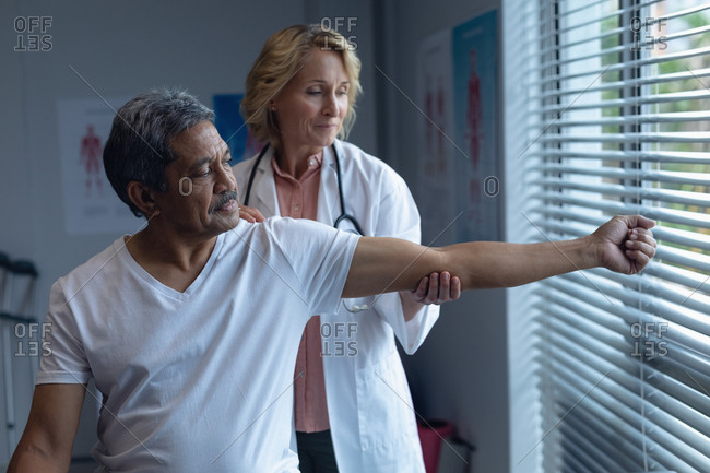 Front view of mature Caucasian female doctor examining senior mixed-race male patient arm in hospital