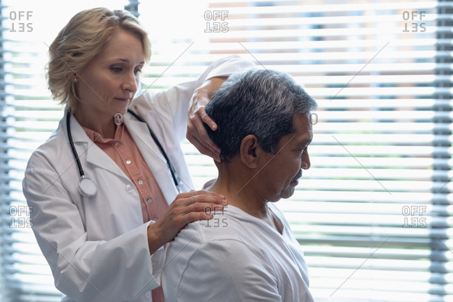 Side view of Caucasian female doctor examining mixed-race male patient neck in hospital