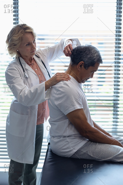 Side view of Caucasian female doctor examining senior mixed-race male patient neck in hospital
