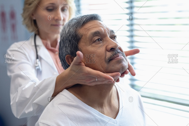 Front view of Caucasian female doctor examining mixed-race male patient neck in hospital