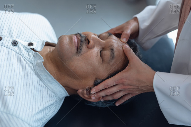 Mid section of Caucasian female doctor examining senior mixed-race male patient in hospital