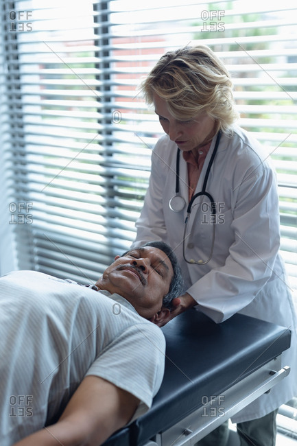 Front view of Caucasian female doctor examining senior mixed-race male patient neck in hospital